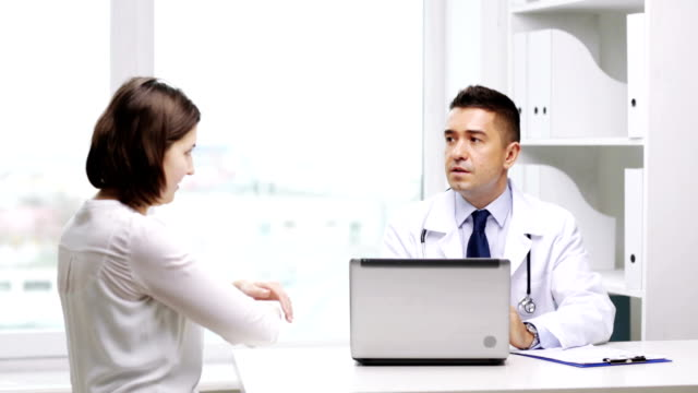 doctor with laptop and woman patient meeting at hospital video