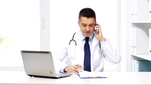 doctor with laptop computer and clipboard calling on smartphone at hospial video