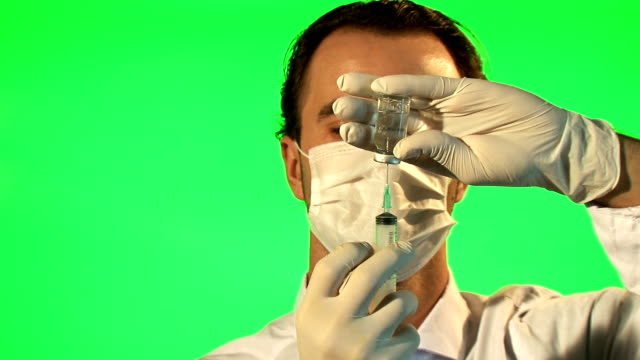Doctor with syringe drawing up clear liquid form bottle video