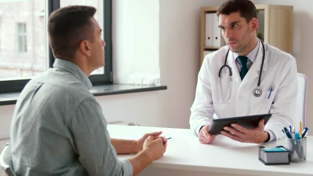 doctor with tablet pc and male patient at hospital medicine, healthcare and technology concept - doctor with tablet pc computer and male patient talking at hospital general practitioner stock videos & royalty-free footage