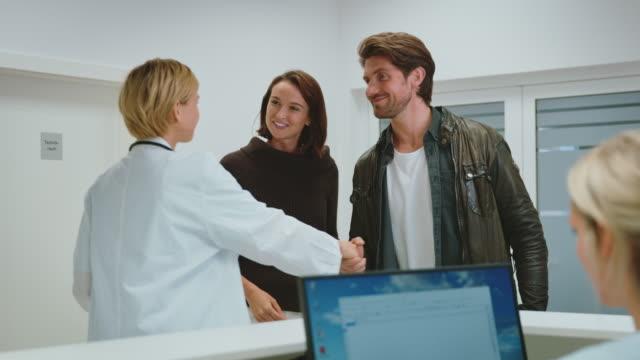 doctor with young couple at reception desk - odejście filmów i materiałów b-roll