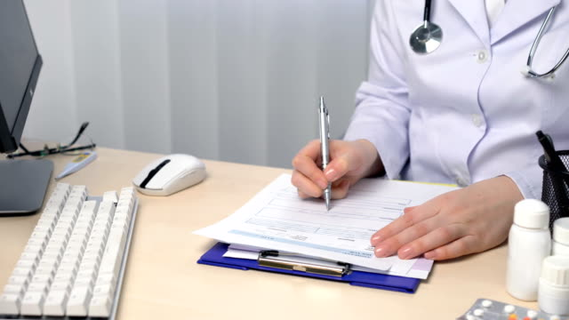 Doctor working in their office, filling out forms, writing a medical report