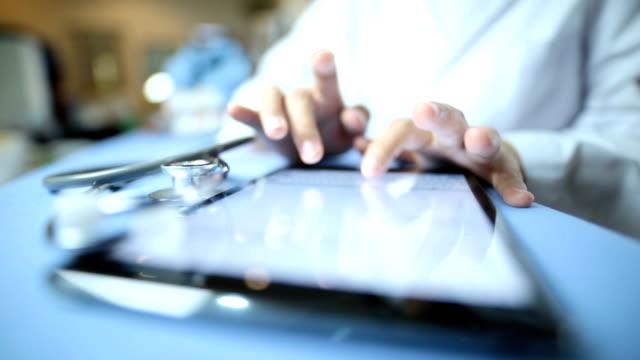 vídeos de stock e filmes b-roll de médico trabalhando em um tablet digital - dossier