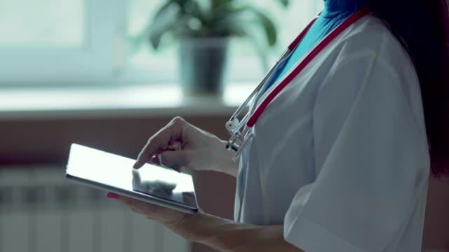 vídeos y material grabado en eventos de stock de médico trabajando en una tableta digital con espacio de copia - electrónica