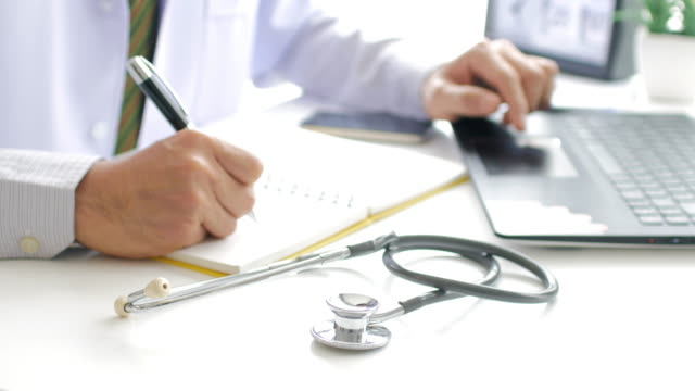 Doctor working with laptop and take a note and filling out medical document video