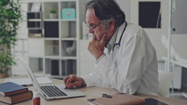 stockvideo's en b-roll-footage met arts werkzaam met laptop - omgeving