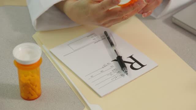 担当医師が書面で設定のデスク、クローズアップ - 処方箋点の映像素材/bロール
