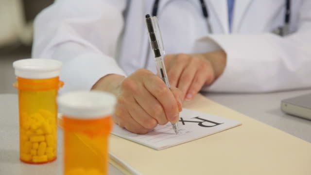 Doctor writing a prescription at desk, close up video