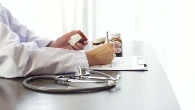vídeos y material grabado en eventos de stock de médico escribiendo una receta en escritorio, primer plano - recipiente para las píldoras