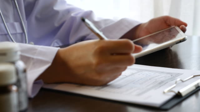 Doctor writing a prescription Medicine on Clipboard with Digital Tablet video