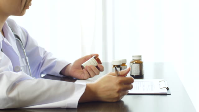 Doctor writing a prescription Medicine on Clipboard with Pill Bottle Doctor writing a prescription Medicine on Clipboard with Pill Bottle, 4K(UHD) Apple ProRes 422 (HQ) 3840x2160 format pill bottle stock videos & royalty-free footage