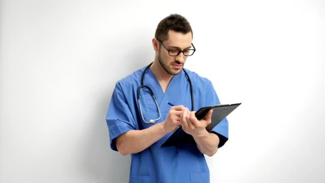 vidéos et rushes de médecin, écrivant dans un presse-papiers - bloc note