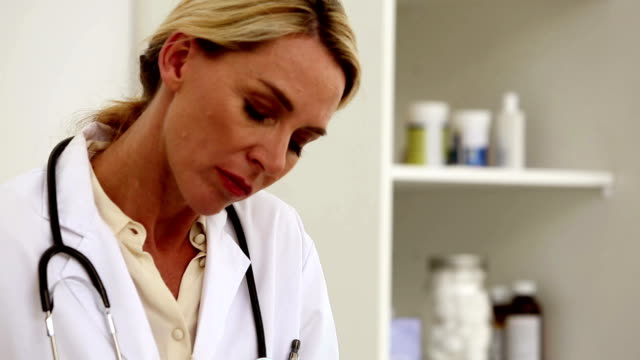 Doctor writing in her office video