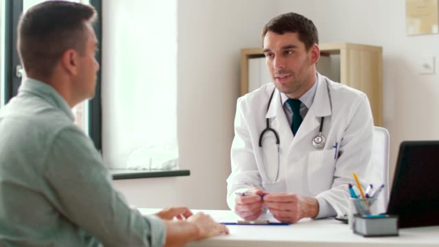 doctor writing prescription for patient at clinic - vídeo