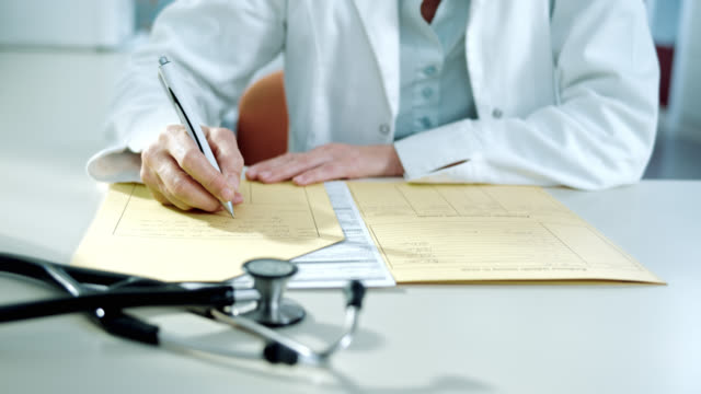 Doctor writing the diagnose into the medical record video