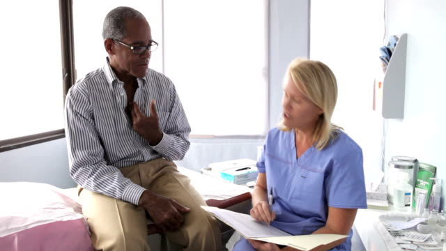 Doctor Writing Up Notes For Middle Aged Male Patient