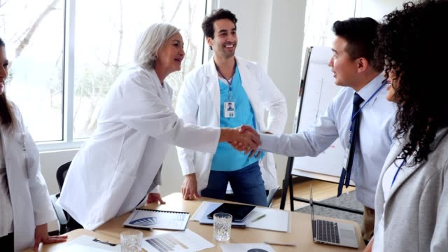 Doctors and hospital administrators meet to discuss hospital business video