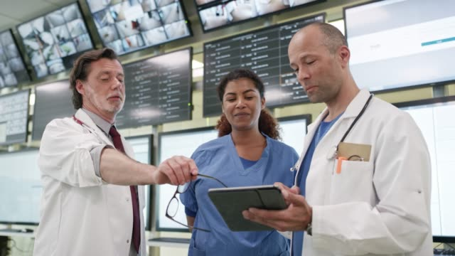 doctors and nurse discussing over digital tablet - collega d'ufficio video stock e b–roll