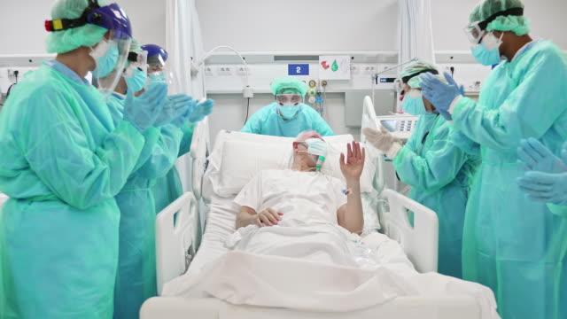 vídeos y material grabado en eventos de stock de médicos y enfermeras aplaudiendo a la unidad de cuidados intensivos de pacientes senior - aplaudir