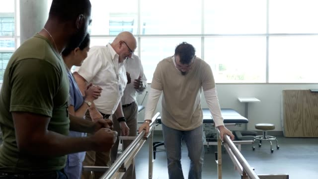 Doctors and patients cheer as a man uses parallel bars to walk after debilitating injury Mid adult Caucasian man slowly walks with the help of parallel bars during rehab from a debilitating injury. His friends, doctors and physical therapist cheer him on as he walks with determination. conquering adversity stock videos & royalty-free footage
