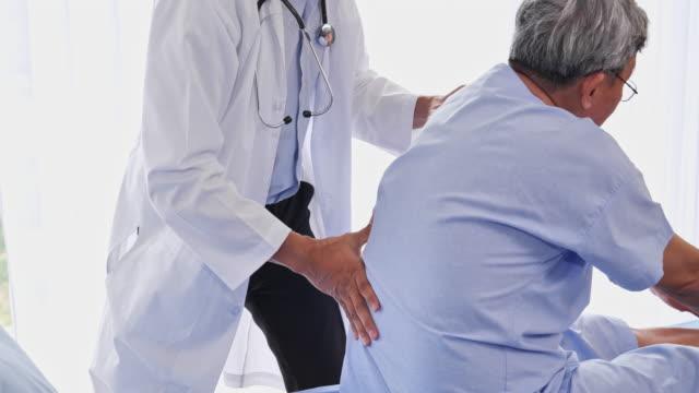vídeos y material grabado en eventos de stock de los médicos están haciendo fisioterapia a la asia mayor del paciente. - quiropráctico