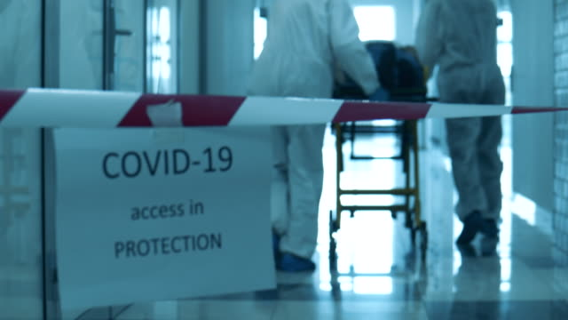 Doctors are taking a patient through a quarantined corridor. Coronavirus concept. video