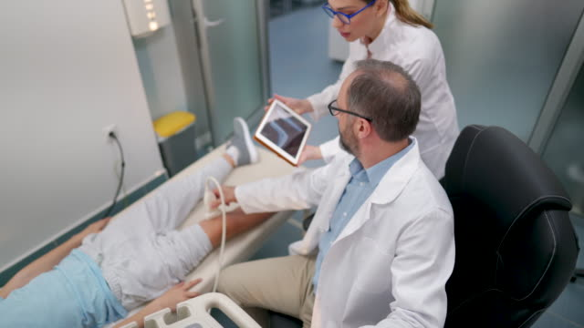 Doctors consulting during ultrasound diagnose Young female doctor and mature male doctor looking at the X-ray scan on digital tablet and discussing during ultrasound examination of the boy's knee orthopedic equipment stock videos & royalty-free footage