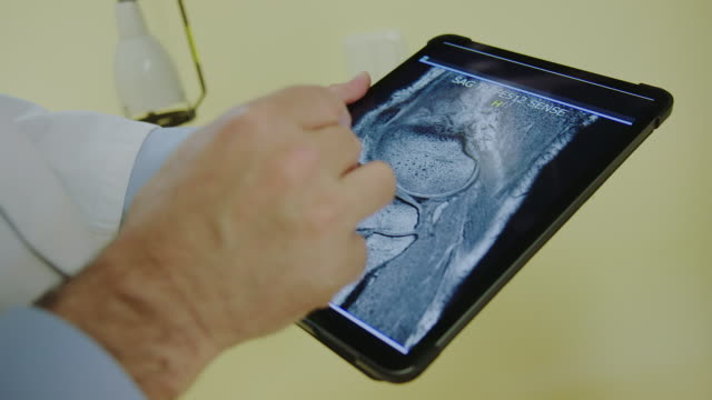 Doctors discussing x-ray scans on digital tablet