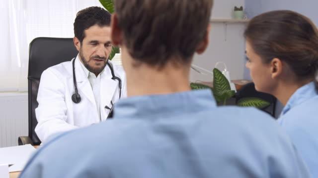 hd dolly: врачи изучения рентгеновского изображения на планшете - debate стоковые видео и кадры b-roll