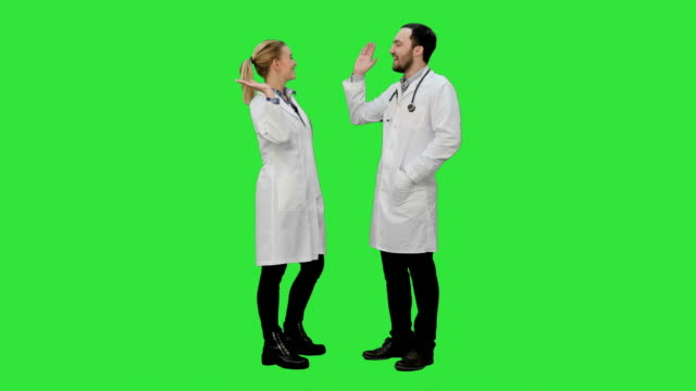 Doctors friends give each other five and thumb up on a Green Screen, Chroma Key video