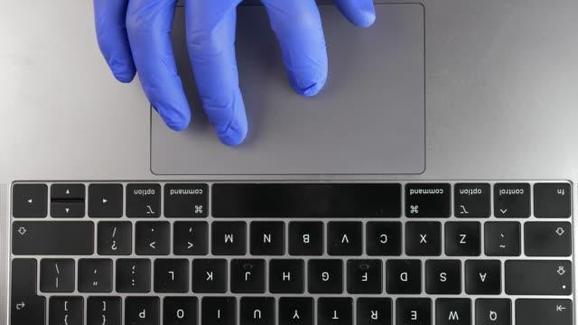 vídeos y material grabado en eventos de stock de mano del doctor en guantes quirúrgicos azules usando trackpad touchpad en office laptop - guante quirúrgico