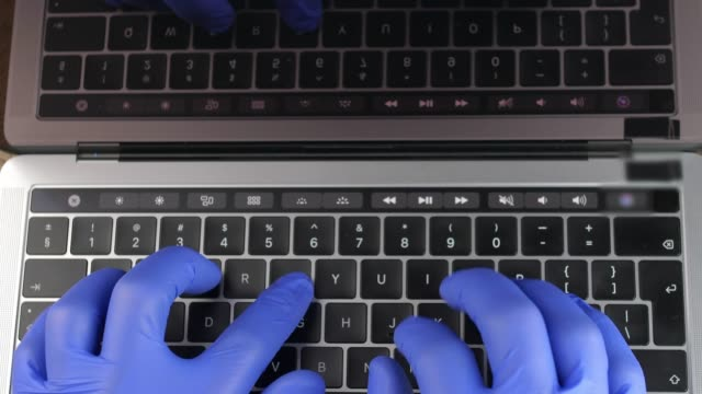 Doctor's Hands in Blue Surgical Gloves Typing on Laptop Keyboard Doctor's Hands in Blue Surgical Gloves Typing on Laptop Keyboard glove stock videos & royalty-free footage
