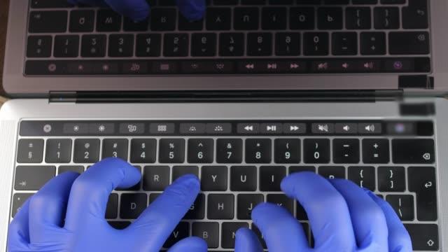 doctor's hands in blue surgical gloves typing on laptop keyboard - rękawiczka filmów i materiałów b-roll