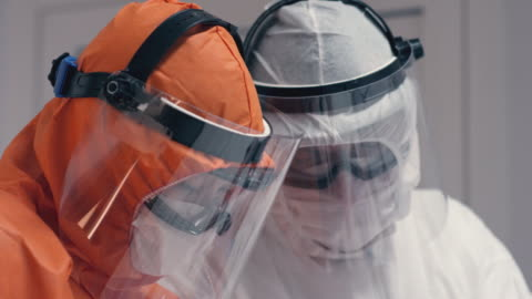 Doctors in Protective Suits Consult Coronavirus Patient's Status - Close Up Dolly Shot Doctors in Protective Suits Consult Coronavirus Patient's Status. Shot in 5K R3D covid stock videos & royalty-free footage