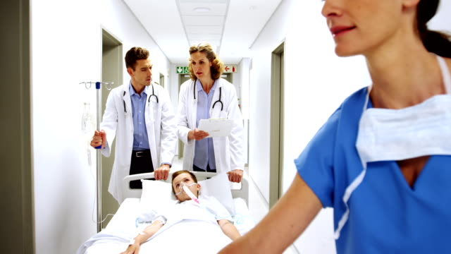 Doctors pushing emergency stretcher bed in corridor Doctors pushing emergency stretcher bed in corridor at hospital stretcher stock videos & royalty-free footage