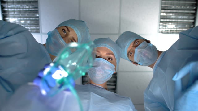Doctors putting oxygen mask on patient face, pov person on operation table