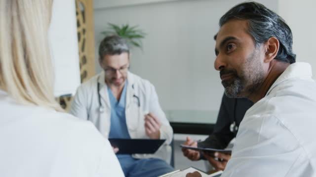 Doctors sit talking in a meeting 4k