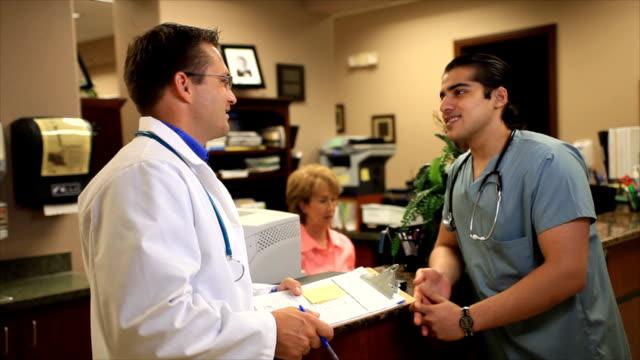 Ärzte sprechen in einem Empfang und Lächeln – Video
