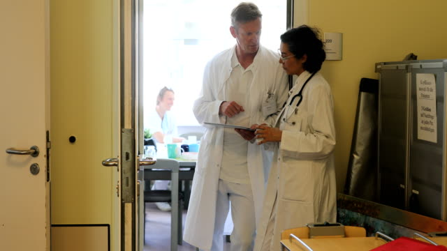 Doctors talking while looking at digital tablet video