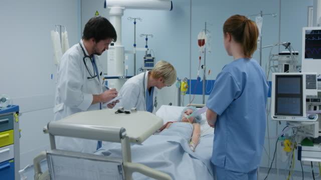 ds läkare besöker ung kvinnlig patient på sin runda på iva - intensivvårdsavdelning bildbanksvideor och videomaterial från bakom kulisserna