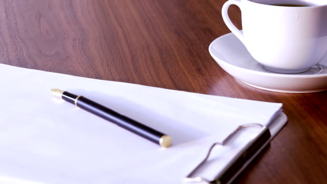 Documents, pen and cup on table video