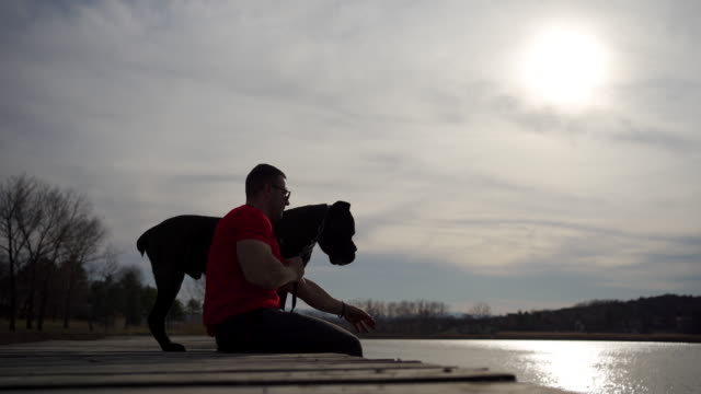 Dog owner sitting at pier on a lake and enjoying his time with his dog