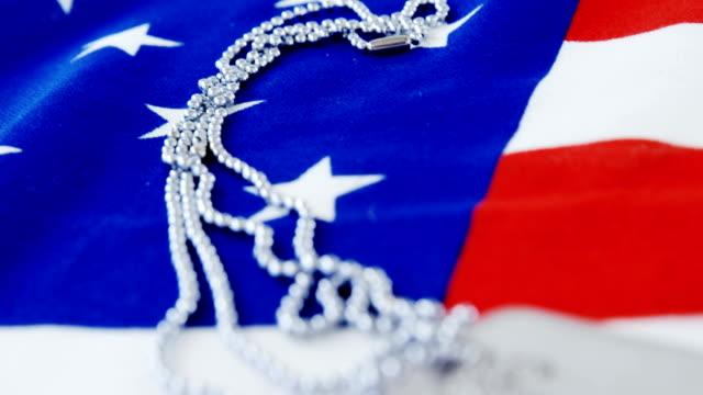 Etiqueta de perro de cadena en una bandera americana - vídeo