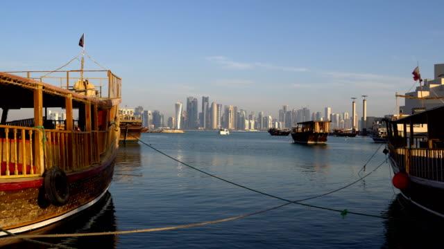 vidéos et rushes de qatar, doha modern city skyline jour shot, moyen orient. vue sur les gratte-ciels de doha avec qatar en bois traditionnels bateaux à broadway de la corniche - doha