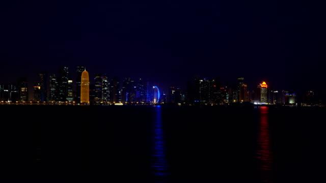 vidéos et rushes de nuit de doha city reflétant dans l'eau de mer du golfe persique, vidéo en temps réel, au qatar, moyen-orient. gratte-ciels illuminés sur une baie ouest reflètent dans une eau du golfe. vue du parc de mia - doha