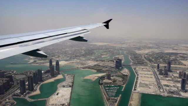 vidéos et rushes de doha, qatar, vu depuis la fenêtre de l'avion à aile - doha