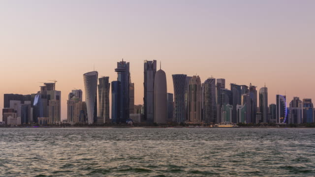 vidéos et rushes de gratte-ciel de doha et le coucher du soleil. time lapse - doha