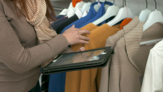 HD DOLLY: Doing An Inventory With Digital Tablet HD1080p: DOLLY shot of a female manager using a digital tablet while doing an inventory in the boutique. saleswoman stock videos & royalty-free footage