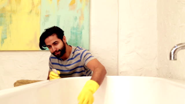 Doing Household Chores Young man cleaning the bathtub. bathroom stock videos & royalty-free footage