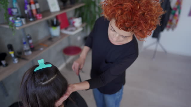 Doing it step by step Brown Woman cutting hair in comfortable, modern  hair salon beautician stock videos & royalty-free footage